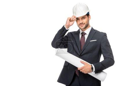 Photo pour Heureux jeune architecte masculin en costume tenant des plans et ajustant le casque dur isolé sur blanc - image libre de droit
