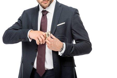 Photo pour Vue partielle d'un homme d'affaires mettant des billets en dollars dans une poche de veste isolée sur du blanc - image libre de droit