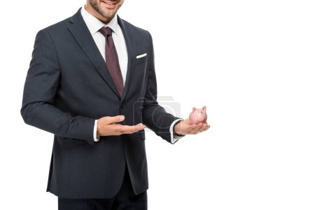 partial view of businessman pointing at pink piggybank isolated on white