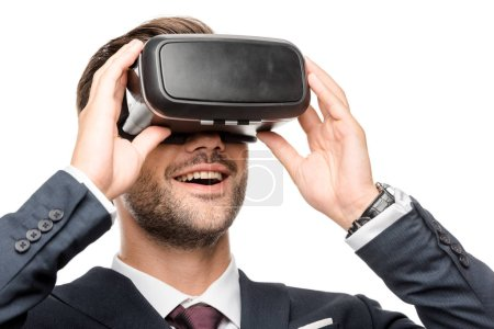 smiling young businessman using virtual reality headset isolated on white
