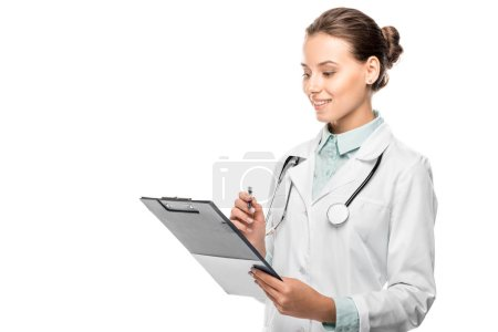 happy young female doctor in medical coat writing in clipboard isolated on white