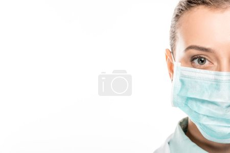 cropped image of young female doctor in medical mask looking at camera isolated on white