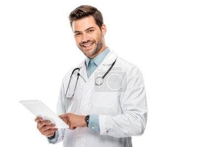 smiling young male doctor in medical coat using digital tablet isolated on white