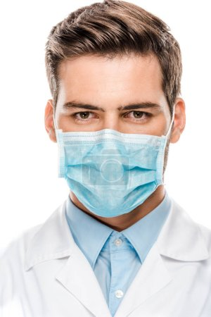 serious young male doctor in medical mask looking at camera isolated on white