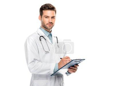 Photo pour Heureux médecin masculin avec stéthoscope sur le cou écriture dans le presse-papiers isolé sur blanc - image libre de droit