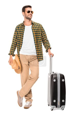 smiling young male traveler in sunglasses standing with wheeled bag isolated on white