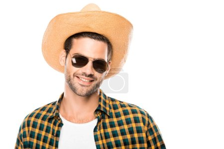 portrait of smiling young male traveler in sunglasses and straw hat looking at camera isolated on white