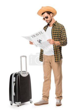 stylish male tourist in sunglasses reading travel newspaper near wheeled bag isolated on white