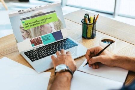 plan recadré de l'homme d'affaires travaillant sur la table avec ordinateur portable et ordinateur portable avec le site Web de la grosse bite noir à l'écran