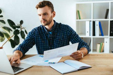 Photo pour Portrait d'homme d'affaires ciblé, faire de la paperasse à table avec ordinateur portable au bureau - image libre de droit