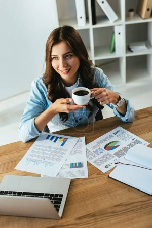 young businesswoman with cup of coffee at workplace with papers and laptop in office