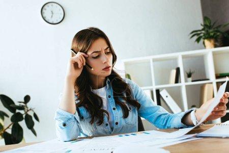 Photo pour Jeune femme d'affaires ciblé, faire de la paperasse sur lieu de travail au bureau - image libre de droit
