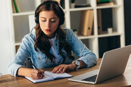 young woman in headphones taking part in webinar in office