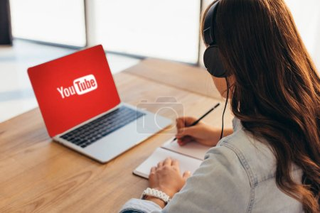 partial view of businesswoman in headphones sitting at workplace with notebook and laptop with youtube website