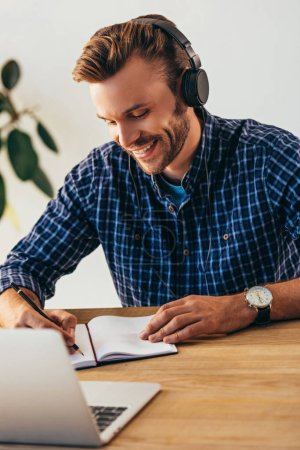 portrait of smiling man in headphones making notes while taking part in webinar at tabletop with laptop in office