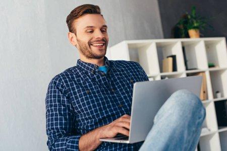 Photo pour Homme d'affaires souriant avec ordinateur portable participant à un webinaire au bureau - image libre de droit