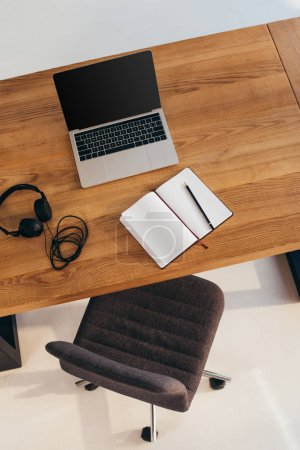 top view of laptop with blank screen, headphones and notebook on wooden table with office chair near by