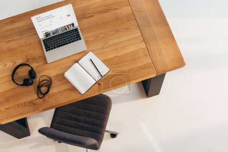 top view of laptop with airbnb website, headphones and notebook on wooden table with office chair near by