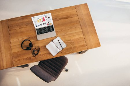 top view of laptop with ebay website, headphones and notebook on wooden table with office chair near by