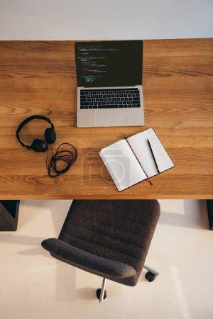 vue de dessus du portable, casque et portable sur la table en bois avec chaise de bureau près de