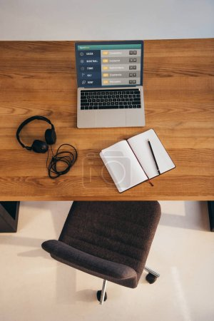 Foto de Vista superior de ordenador portátil, auriculares y cuaderno en la mesa de madera con silla de oficina cerca de - Imagen libre de derechos