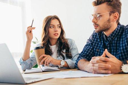 Photo pour Collègues d'affaires participant à un webinaire sur table avec des papiers et un ordinateur portable au bureau - image libre de droit