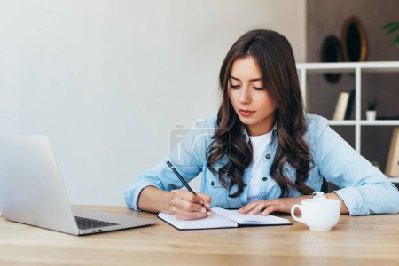 young woman at tabletop with laptop taking part in webinar in office