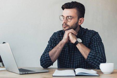 Porträt eines nachdenklichen Geschäftsmannes am Arbeitsplatz mit Laptop und Notizbuch