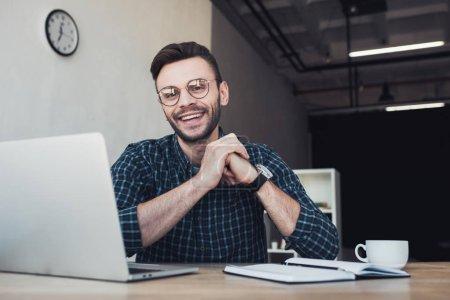 Photo pour Portrait d'homme d'affaires gai sur lieu de travail avec ordinateur portable et ordinateur portable au bureau - image libre de droit