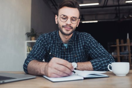 portrait of businessman making notes in notebook at workplace in office