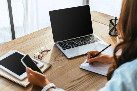 vista parcial de mujer con smartphone participar en webinar en mesa con ordenador portátil