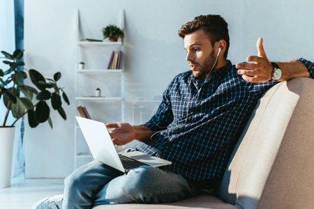 emotional man in earphones taking part in webinar at home