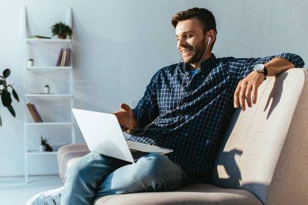 cheerful man in earphones taking part in webinar at home