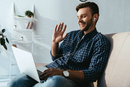 smiling man in earphones greeting someone while having video call at home