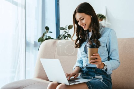 smiling woman with coffee to go on sofa taking part in webinar at home