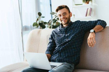Photo pour Portrait d'un homme souriant en lunettes avec un ordinateur portable assis sur un canapé à la maison - image libre de droit