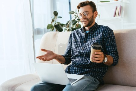 emotional man with coffee to go and laptop taking part in webinar at home