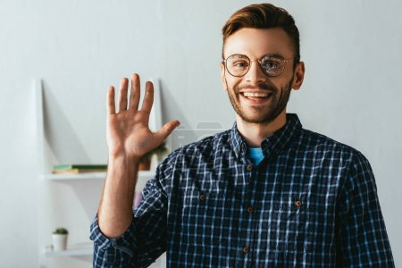 portrait of cheerful man in eyeglasses waving to camera at home