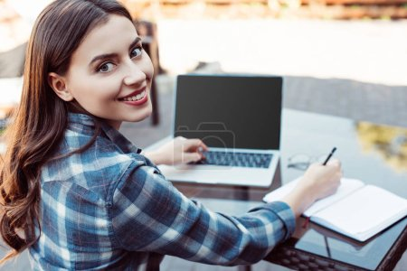 Photo for Smiling beautiful girl taking part in webinar at table in street cafe - Royalty Free Image