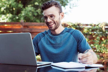 smiling handsome man taking part in webinar outdoors