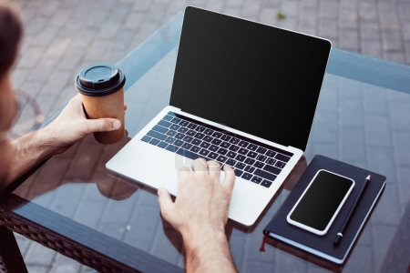 Photo for Cropped image of man using laptop with blank screen at table in street cafe - Royalty Free Image