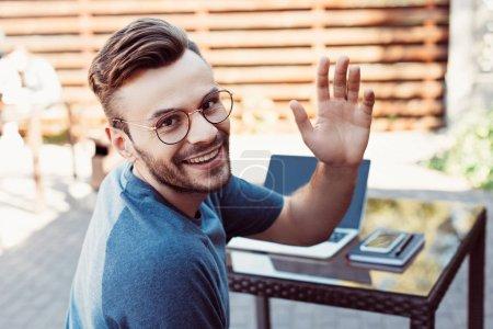 smiling handsome man waving hand and looking at camera at street cafe