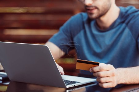 cropped image of man shopping online with credit card and laptop at table