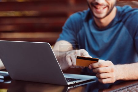 cropped image of man shopping online with credit card and laptop at table at street cafe