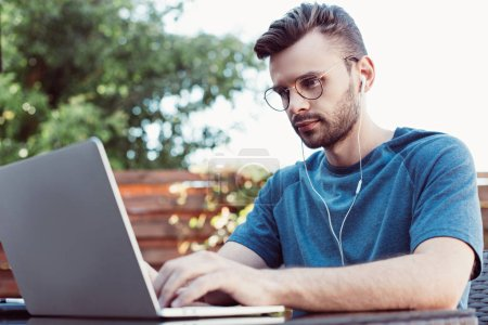 handsome man taking part in webinar at table in park