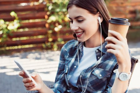 smiling attractive woman listening music with smartphone on street and holding coffee in paper cup