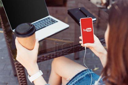 woman using smartphone with youtube appliance at table and holding coffee in paper cup