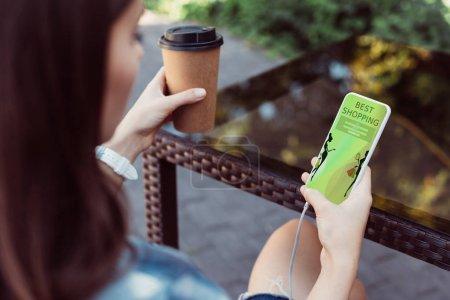 Photo pour Femme à l'aide de smartphone avec les meilleures boutiques appareil à table et tenant le café dans la tasse de papier - image libre de droit