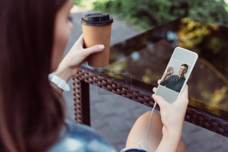 colleagues having video chat with smartphone outdoors
