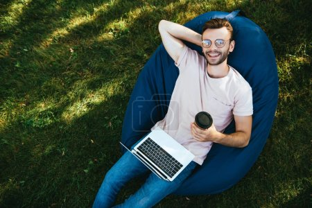 high angle view of smiling handsome man taking part in webinar and lying on bean bag chair in park